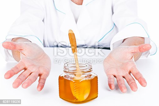 Hands of doctor offering honey to the viewer. Front view