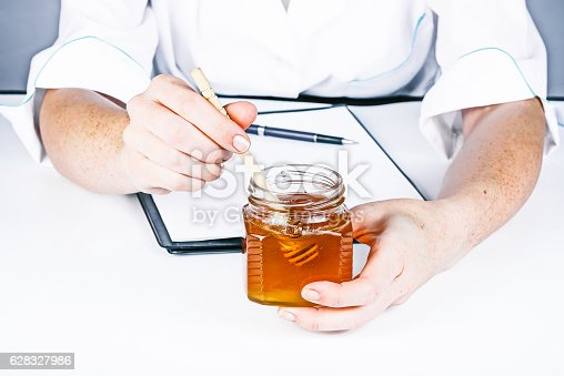 Hands of doctor giving honey and prescription to the viewer. Front view