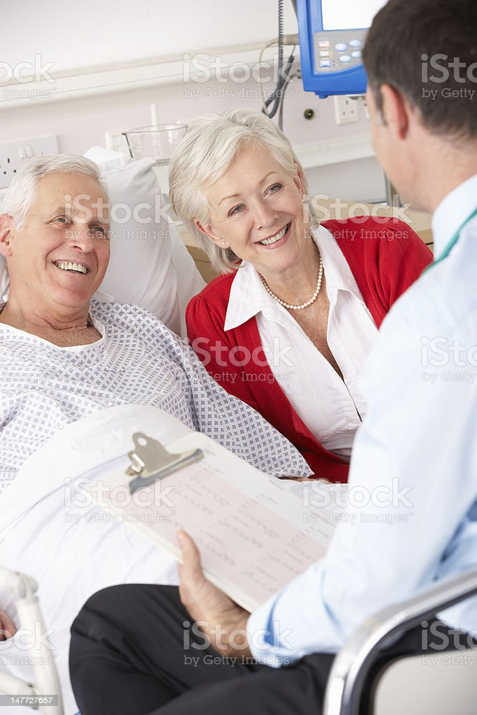 Doctor going over health record with senior couple royalty-free stock photo