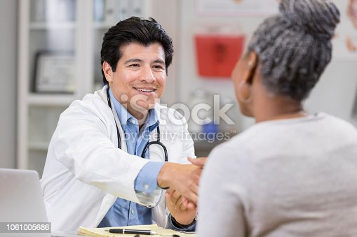 A smiling mid adult male doctor sits at his office desk across from an unrecognizable new patient.  He shakes hands with her.