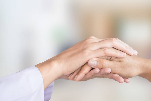 doctor hand comforting patient in a hospital room background - comfort stock photos and pictures