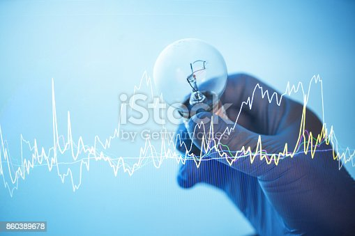 istock doctor hand hold a electric lamp with stock chart graph 860389678