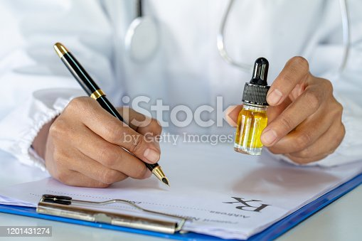 istock doctor hand hold and offer to patient medical marijuana and oil.  legal light drugs prescribe, alternative remedy or medication, medicine concept.  CBD oil hemp. 1201431274