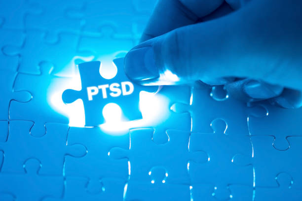 Doctor hand holding a jigsaw puzzle with PTSD - post traumatic stress disorder. War veteran mental health issue word. Concept Healthy. stock photo