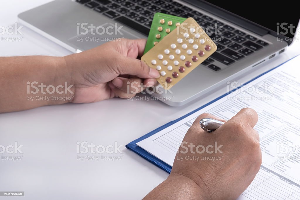 doctor hand holding birth control pills stock photo