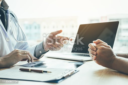 873418972istockphoto Doctor hand holding pen and talking to the patient about medication and treatment. 1133092724