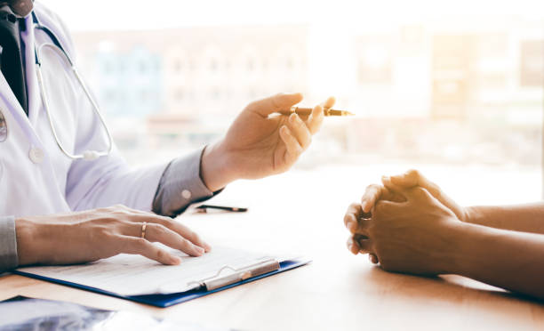 Doctor hand holding pen and talking to the patient about medication and treatment. stock photo