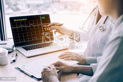 873418972istockphoto Doctor hand holding pen pointing on laptop screen and talking to the patient about medication and treatment. 935298046
