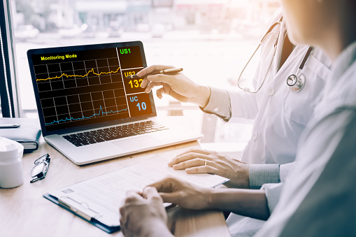 873418972 istock photo Doctor hand holding pen pointing on laptop screen and talking to the patient about medication and treatment. 935298046