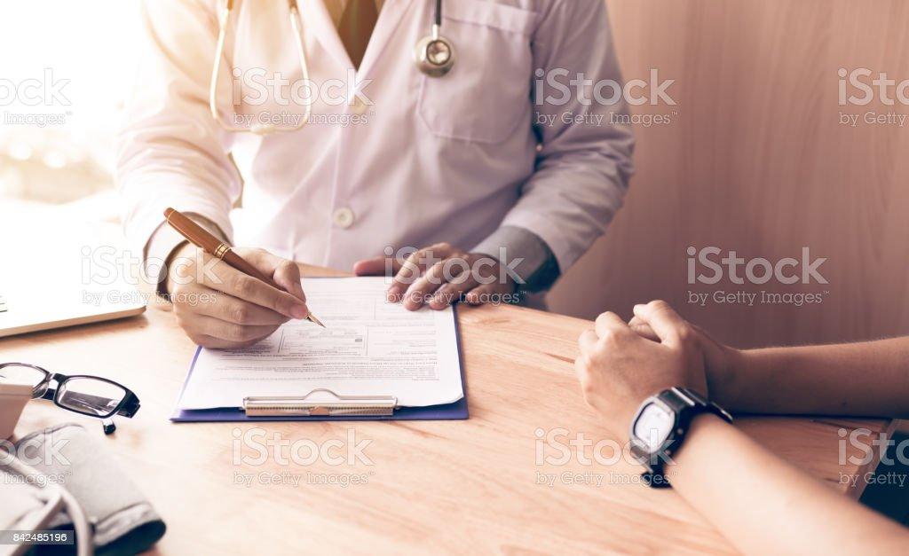 医師の手がペン メモ帳に患者履歴の一覧を書くと薬物および処置の患者に話を持ちます。 ストックフォト