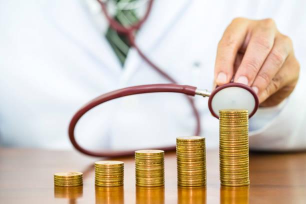 Arzt-Hand mit Stethoskop Überprüfung Stapel von Geld Münzen angeordnet als Grafik auf Holztisch, Konzept der finanziellen Gesundheit und Arztkosten – Foto