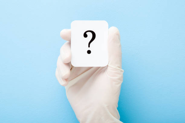 Doctor hand in white rubber protective glove showing question mark. Light blue background. Concept of medical issues. Closeup. Top down view. stock photo