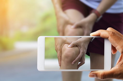 Doctor hand used smart phone take photo of Asian woman use hands hold on her knee injury.