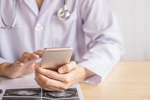 istock doctor hand using smart phone while working at hospital 957656280