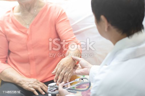 istock Doctor hand with stethoscope check up elderly woman people. Old aging female seeing medical physician in clinical healthcare hospital. 1148520516