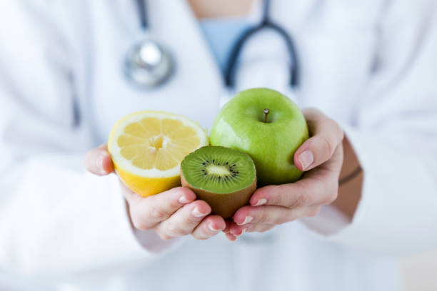 doctor hands holding fruit such as apple, kiwi and lemon. - dietician stock pictures, royalty-free photos & images