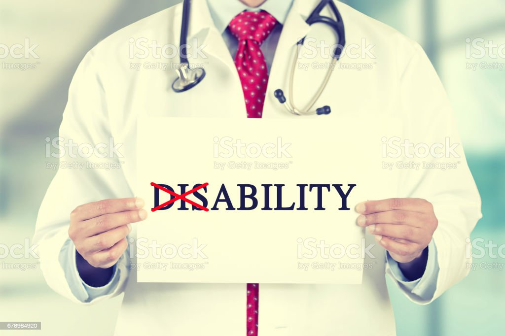 doctor hands holding white card sign with disability crossing through the Dis with a red marker text message stock photo