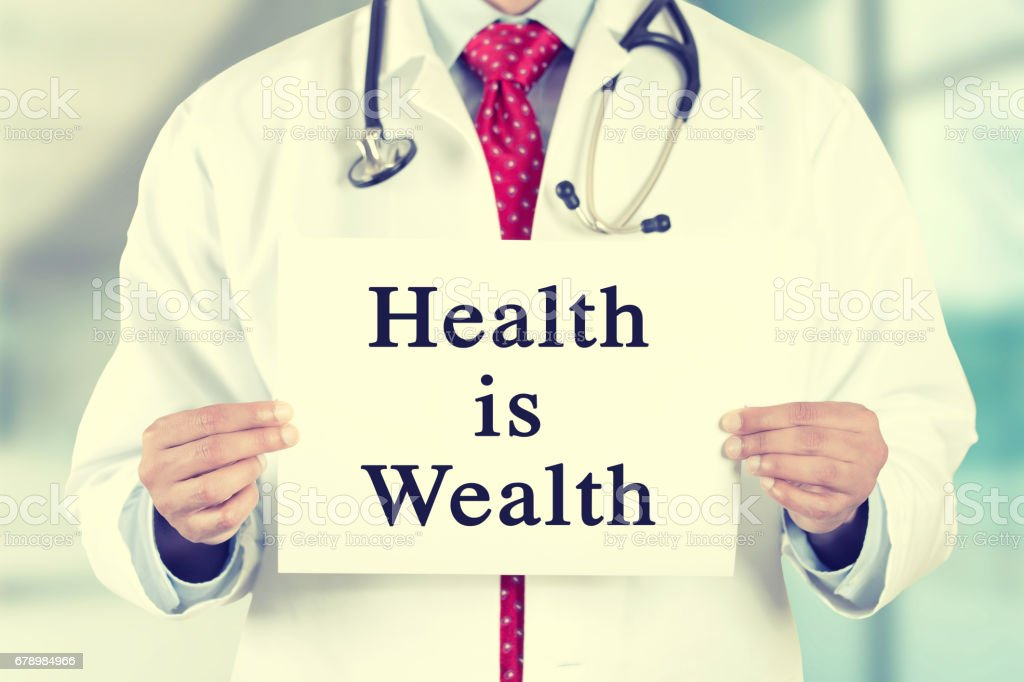 doctor hands holding white card sign with health is wealth text message stock photo