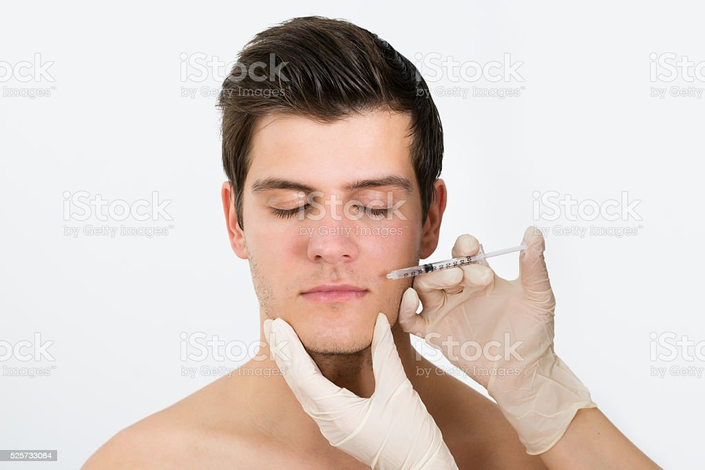 Doctor Hands Injecting Botox Injection In Man Face stock photo