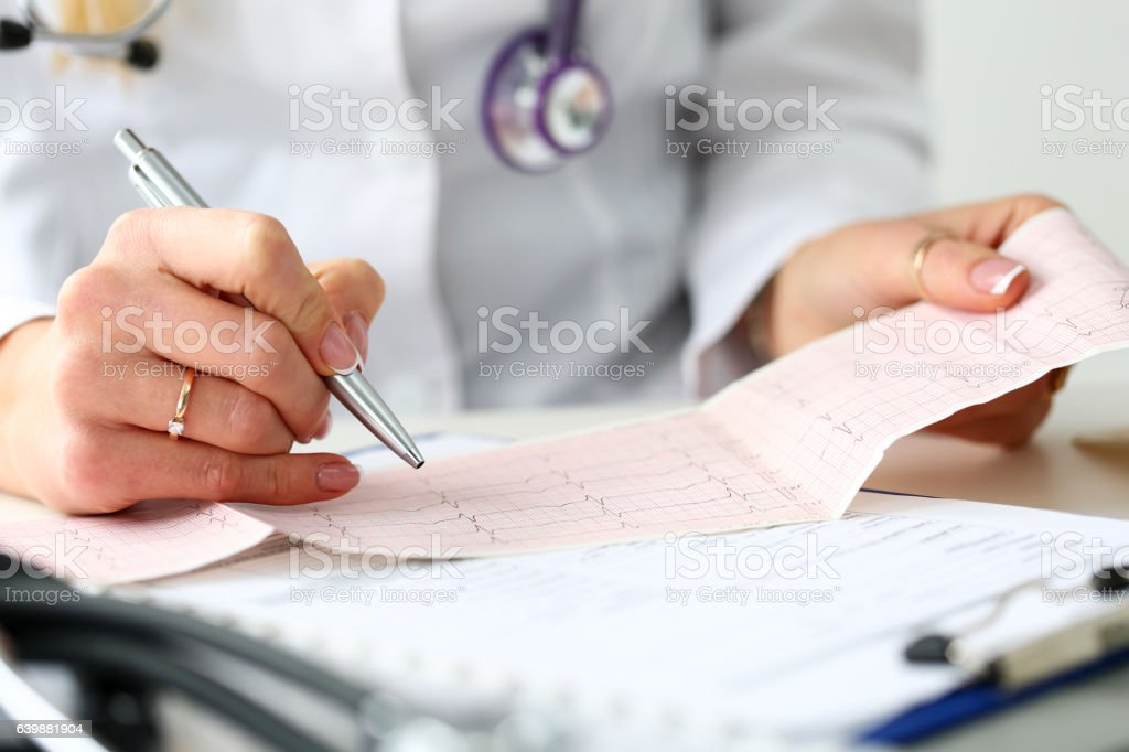 Doctor hands with cardiogram chart on clipboard pad - Photo
