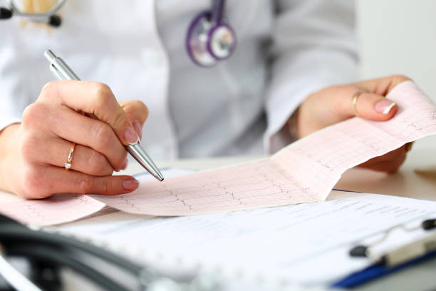Doctor hands with cardiogram chart on clipboard pad – Foto