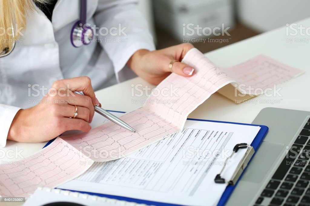 Doctor hands with cardiogram chart on clipboard pad stock photo