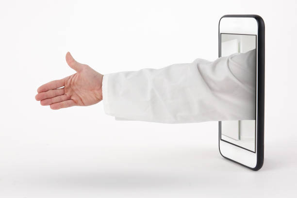 Doctor handshake with arm coming out of the phone - foto stock