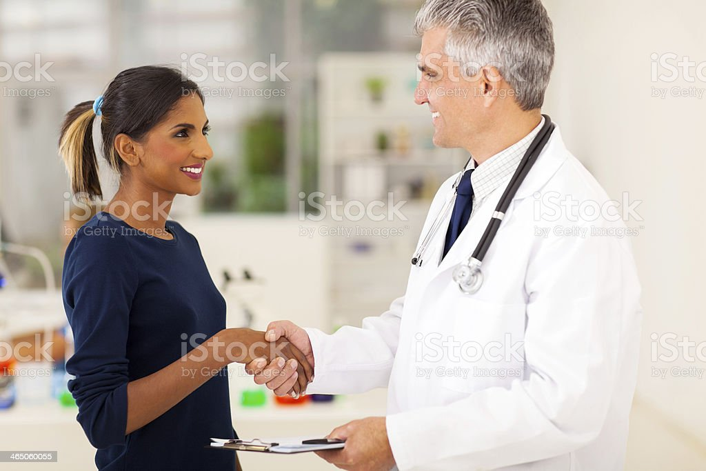 doctor handshaking with young patient stock photo