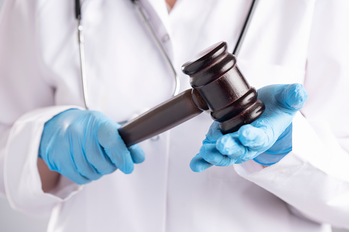 Doktor's hands with blue glove are hanging a gavel.