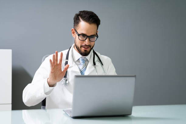 Doctor Having Video Conference On Laptop stock photo