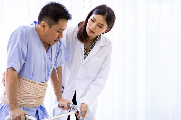 doctor help elderly using adult walker - inpatient stock pictures, royalty-free photos & images