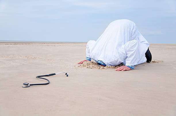 Doctor hiding head in sand Doctor hiding head in sand. In the front a stethoscope.have a look at different variations: head in the sand stock pictures, royalty-free photos & images