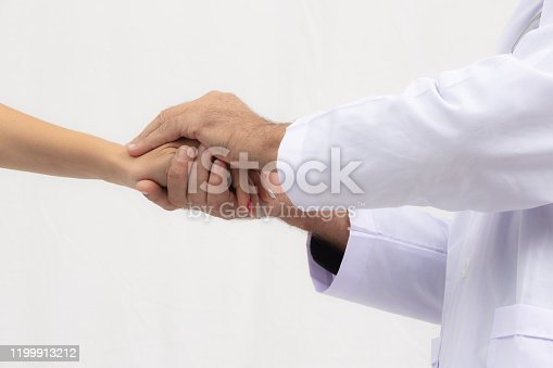 1133353454istockphoto doctor hold patient hand in office 1199913212