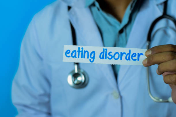 Doctor holding a card with text eating disorder. stock photo