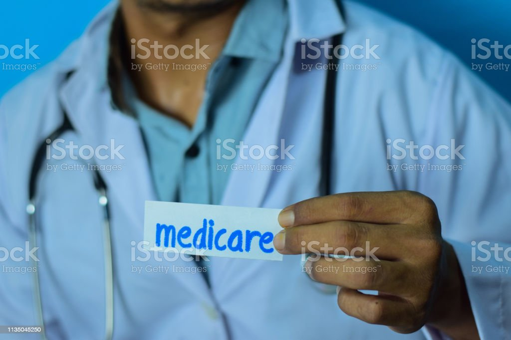 Doctor holding a card with text medicare. Medical and healthcare...