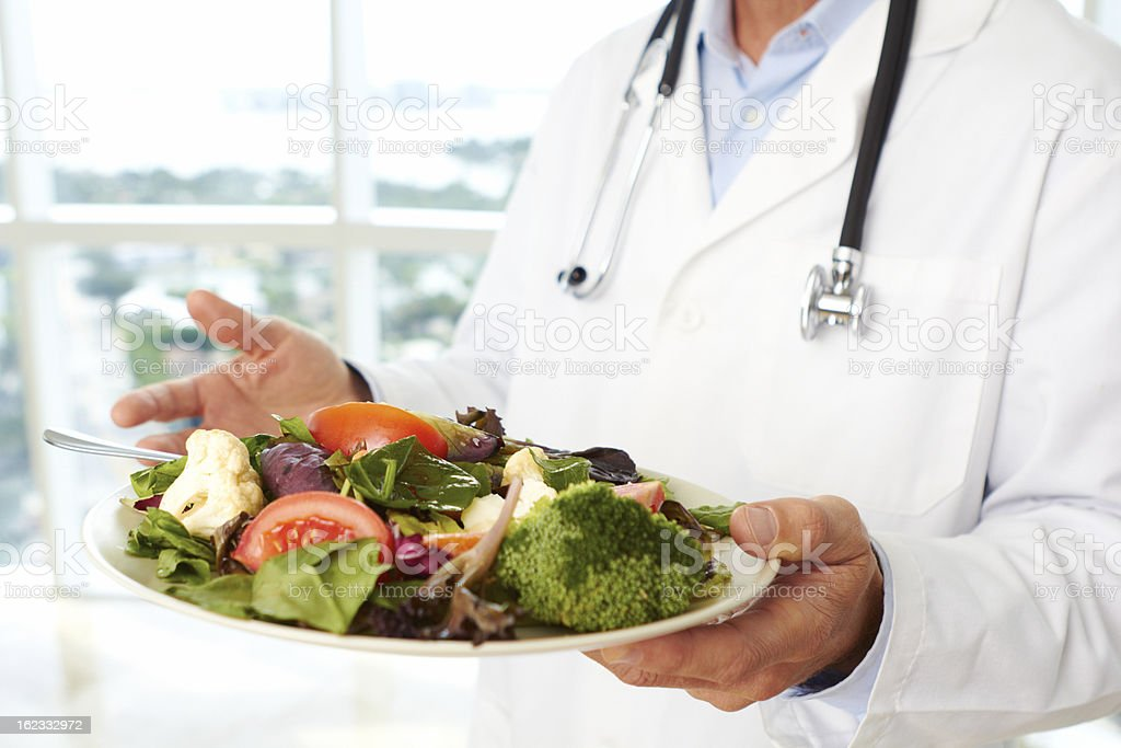 Doctor holding a fresh salad royalty-free stock photo