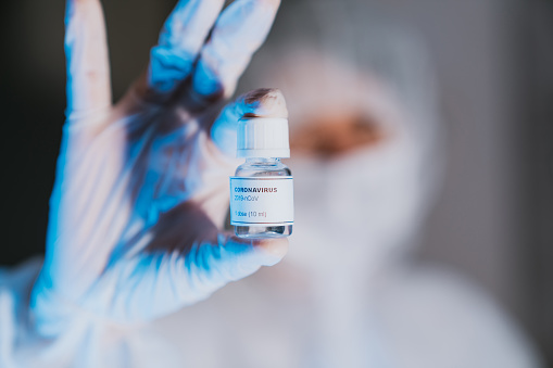 Doctor holding a vial of coronavirus COVID-19 vaccine