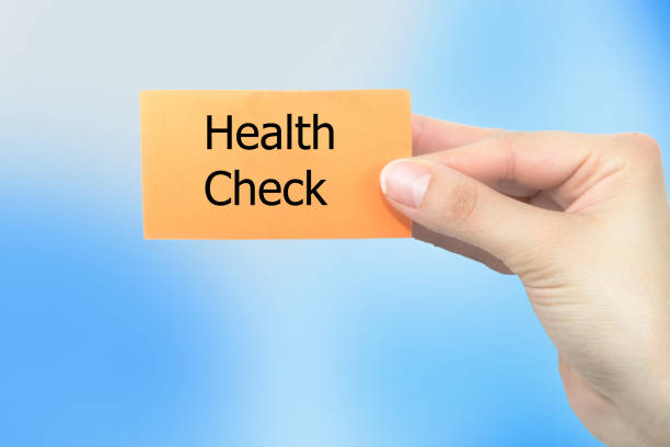 Doctor holding a white paper with Health check sign on the display stock photo
