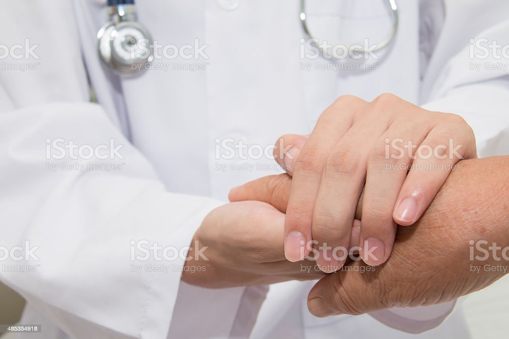 Doctor holding an old woman's hand stock photo