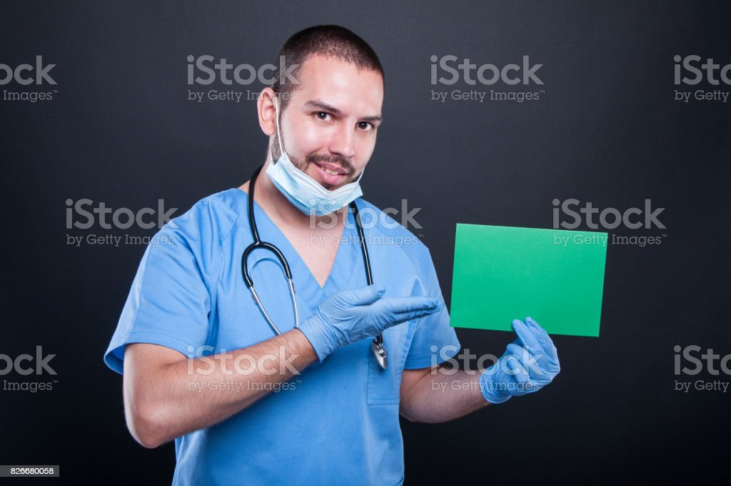 Doctor holding and showing green copypsace card stock photo