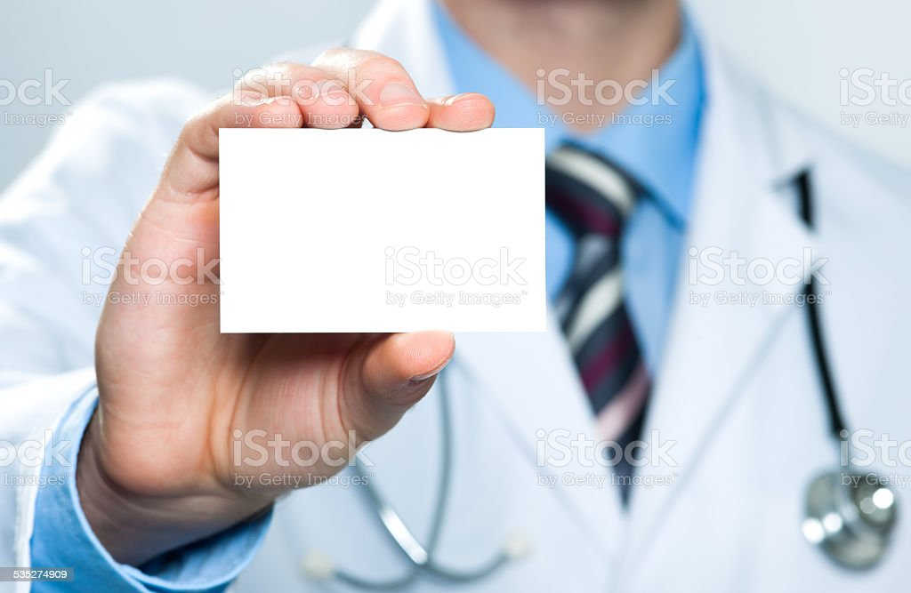 Doctor holding blank business card stock photo