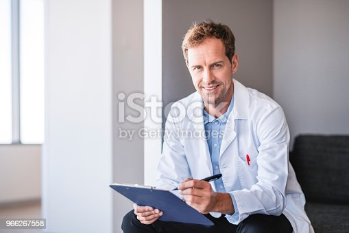 Portrait of mid adult doctor holding clipboard and pen in hospital. Confident male healthcare worker is smiling. He is wearing lab coat while sitting in clinic.