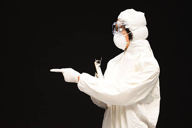 Doctor holding clipboard & pointing away stock photo