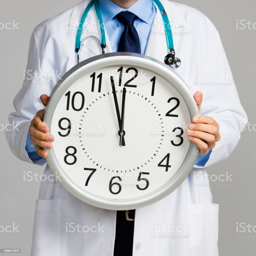 Doctor Holding Clock stock photo