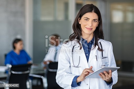 Portrait of beautiful mature woman doctor holding digital tablet and looking at camera. Confident female doctor using digital tablet with colleague talking in background at hospital. Latin nurse in labcoat and stethoscope in private clinic with medical team working.