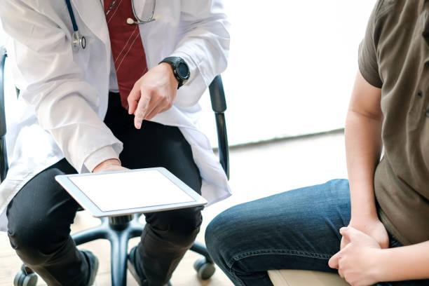 doctor holding digitale tablet praten en uit te leggen over de behandeling van mannelijke patiënten. behandelen van patiënten met prostaatkanker. - prostaatkanker stockfoto's en -beelden
