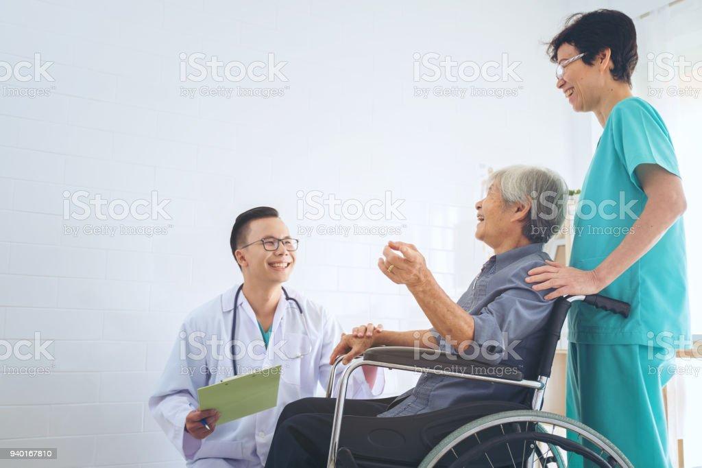 Arzt hält Hand ältere Patienten im Rollstuhl, die Unterstützung von seinem älteren Patienten. – Foto