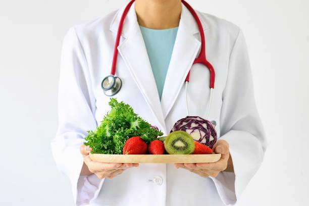 Doctor holding fresh fruit and vegetable, Healthy diet, Nutrition food as a prescription for good health. stock photo