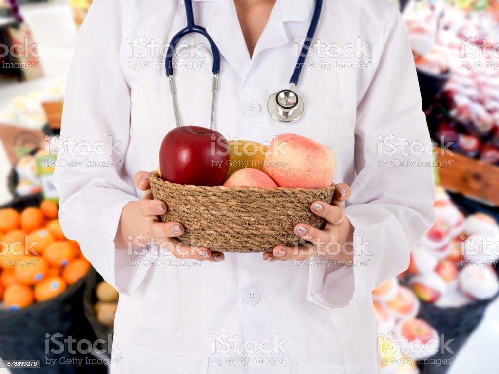 Médico con fruta fresca de frutas en el fondo del supermercado borrosa - foto de stock