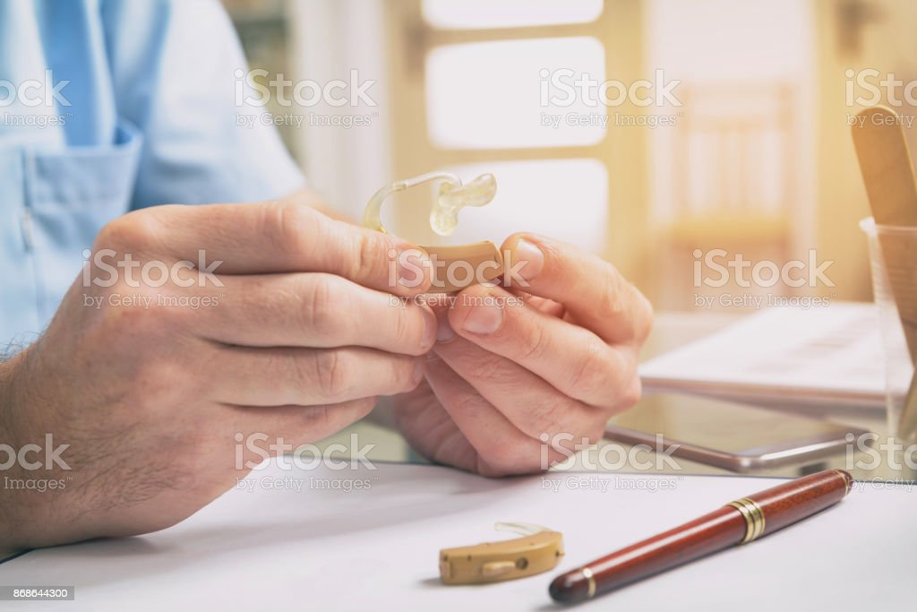 Doctor holding hearing aid - foto stock